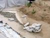 Hier zu sehen der Aufbau der unterirdischen Sperrschicht: Folie, Kies, Vlies.