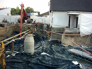 Zwischen die Eisenträger (links) kommen Holzbalken - so entsteht eine Stützmauer.